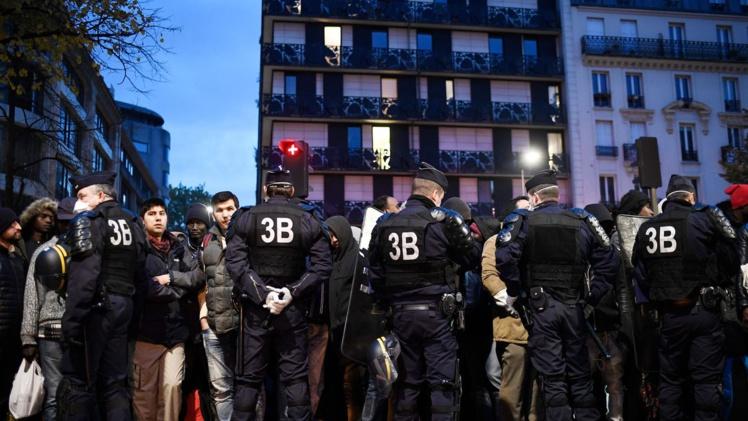 Des policiers entourent des migrants pendant l'évacuation du camp installé entre les stations de métro Stalingrad et Jaurès à Paris le 4 novembre 2016  afp.com/LIONEL BONAVENTURE
