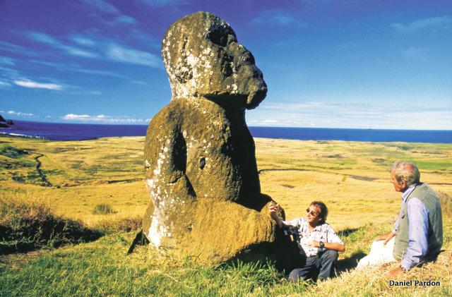 """Un document précieux : l'archéologue chilien Claudio Cristino et l'apnéiste français Jacques Mayol (lors de son dernier voyage dans le Pacifique, peu avant son décès) au pied du """"tiki"""". Pour le scientifique, il ne fait guère de doute que la statue est postérieure aux grands moai. A gauche, en bord de mer, on distingue l'alignement de moai de l'ahu Tongariki, restauré par ce même Claudio Cristino."""