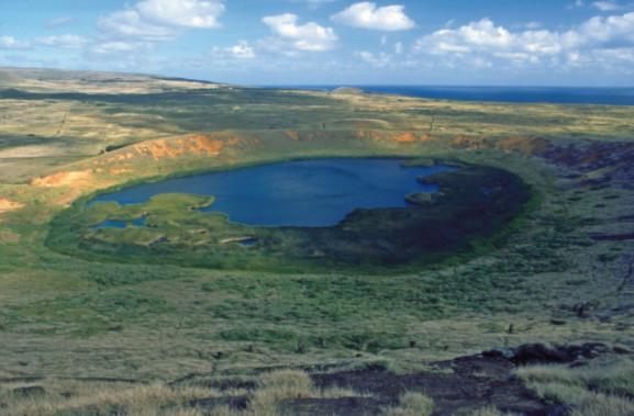 Une vue du cratère du Rano Raraku ; le lac est un lieu de baignade. Sur la pente, on distingue des têtes de moai, émergeant de l'herbe haute.