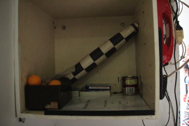 Dans une étagère, à côté de la porte d'entrée, des jeux de cartesn des balles de ping-pong et un damier.