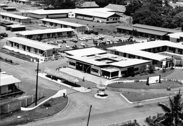 Vue aérienne de l'entrée principale du camp d'Arue CEP, sur la route de ceinture, en 1960. Au fond, les collines de Erima. Photo Daniel