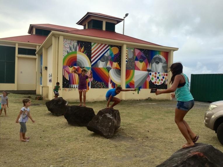 Les jeunes jouent devant le mur peint par le grand Urban artiste espagnol Okuda.
