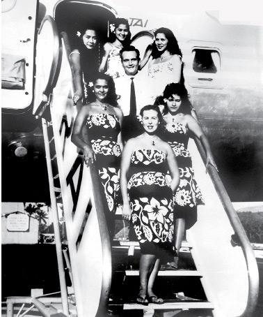 Photo de groupe des personnels RAI-TAI sur l'échelle du DC 7 C. En haut et de gauche à droite, Jeanne Teriitehau-Navarro, Madeleine Sannen et Annie Toomaru-Hirshon toutes trois navigantes. Au centre, Paul Grigorieff, chef d'escale, à gauche, Rose-Mary Sanquer-Blouin, Maguy Malinowski et Galina Grigorieff.