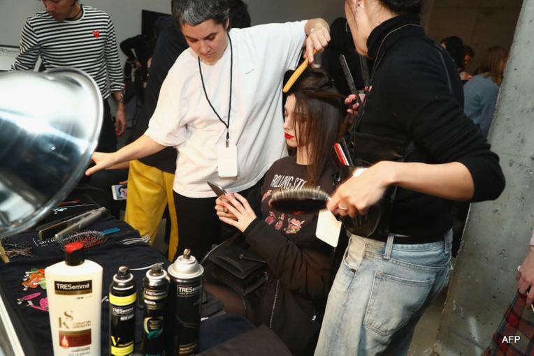 Une top model aux bons soins des esthéticiennes, coiffeuses, manucures et maquilleuses dans les coulisses de la New York Fashion Week 2018 (crédit photo : AFP)