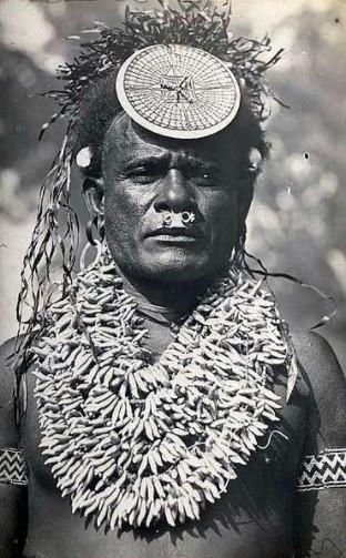 Un chef salomonais avec ses parures : sur la tête, un kap-kap fait d'une écaille de tortue ciselée sur un disque en coquillage ; sur la poitrine, d'impressionnants colliers en dents de dauphins, témoignages de sa puissance au sein de son clan.