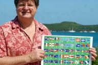 Photo d'archives: Jean-Raymond Postic, membre du comité de pilotage sur les signes identitaires, pose avec un dépliant où figurent plus de 80 idées de drapeaux pour la Nouvelle-Calédonie, le 20 avril 2007 à Nouméa. Alors que l'identité nationale a