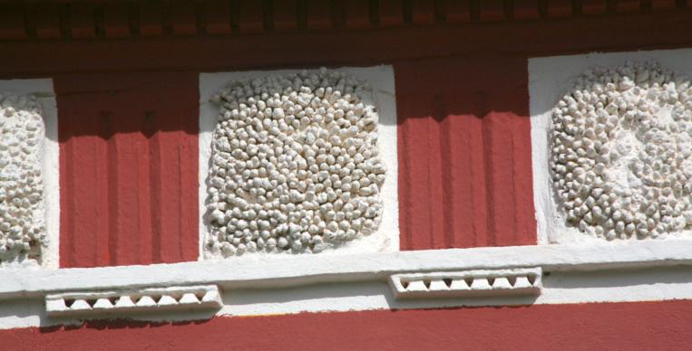 Détail d'une frise de la façade extérieure de la cathédrale, au-dessus du portail d'entrée : des blocs de coraux du genre Acropora ont été noyés dans la chaux.