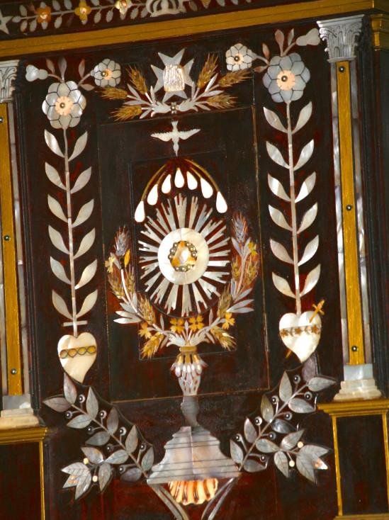 Trois couleurs de nacre (Pinctada margaritifera) ont été utilisées pour le tabernacle ; on remarque également à sa base un fragment de coquille de pu (Charonia tritonis).