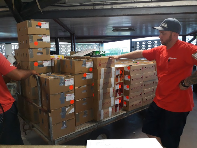 Les cartons sont pesés de nouveau par les agents d'Air Tahiti, avant d'être embarqués dans l'avion.