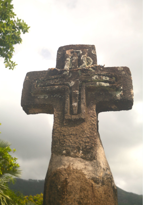 Une croix de pierre dressée sur la route du bord de mer indique l'entrée de la Mission catholique.
