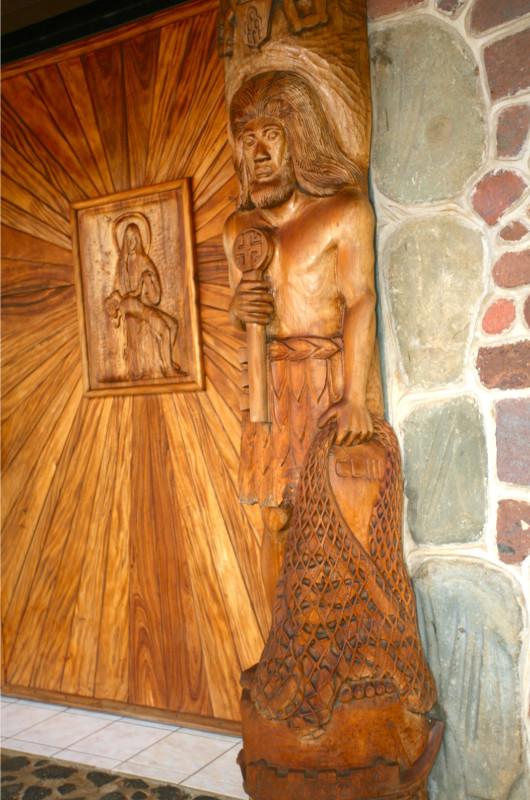 La porte d'entrée est composée de deux panneaux ; sur celui-ci Saint Pierre tient un filet avec 17 poissons.