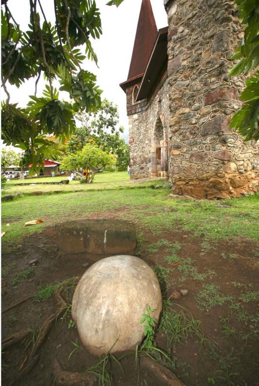 """À l'image de l'œuf qui symbolise """"te pito"""" à l'île de Pâques, voici un autre """"pito"""" marquisien, galet de plage sphérique posé devant l'entrée de la cathédrale. Imposition des mains pour ceux en quête de """"mana""""…"""