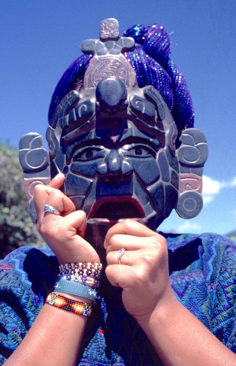 Une jeune Indienne Kakchiquel s'est caché derrière un masque mortuaire, réplique d'une pièce provenant d'une tombe de Tikal.