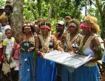 Aux Îles Salomon, des femmes tiennent un système à diodes électroluminescentes (DEL) photovoltaïque