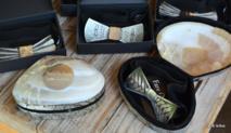"""35 modèles différents de nœuds papillon en nacre ont été créés par les graveurs locaux partenaires de l'entreprise Fare O Pepe. Leurs prix varient de 124 euros (14 650 francs) à 389 euros (46 000 francs). Chaque nœud papillon est unique et livré avec une perle pour """"rappeler l'origine de la nacre perlière""""."""
