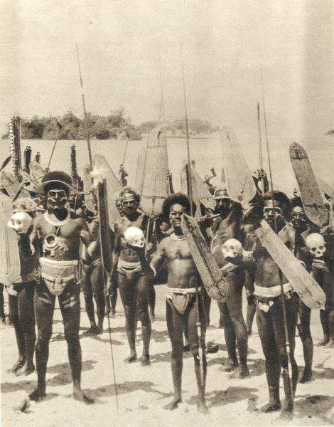 Cette photo ancienne de guerriers salomonais représente des chasseurs de têtes exhibant des crânes pris à leurs ennemis.