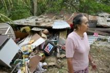 Une femme devant sa maison détruite par le cyclone Oli ( Photo AFP Gregory Boissy)