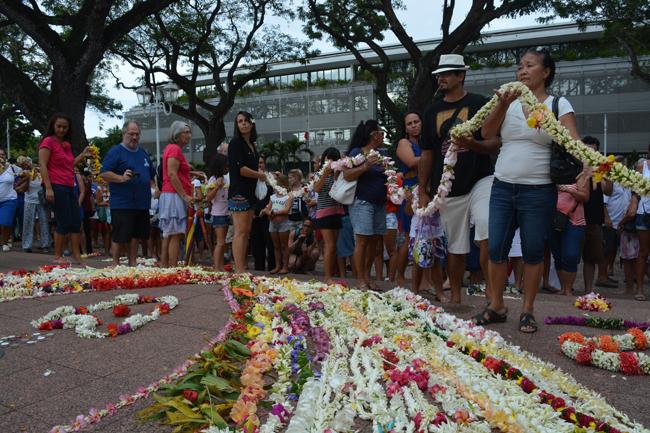 Un tapis de couronnes de fleurs déposé devant le monument aux morts.