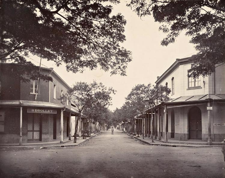 La rue de la Petite-Pologne en 1900. A gauche le magasin général en briques de Sosthène Drollet, l'inventeur de la gelée de goyave, qui est devenue en 1938 la pharmacie Jacquier. Photo Holmes