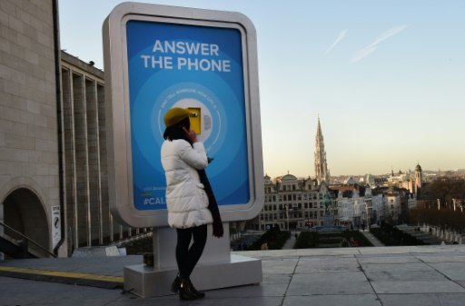 Une femme répond, le 8 janvier 2016, à un téléphone public installé à Bruxelles pour permettre aux gens d'interroger un habitant de passage pour obtenir des informations sur la sécurité de la ville