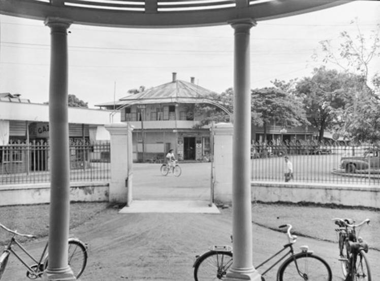 La place de la cathédrale en 1952 vue de l'entrée de la banque d'Indochine, avec en face la construction en bois à l'emplacement de l'actuelle pharmacie de la cathédrale. Photo Whites Aviation