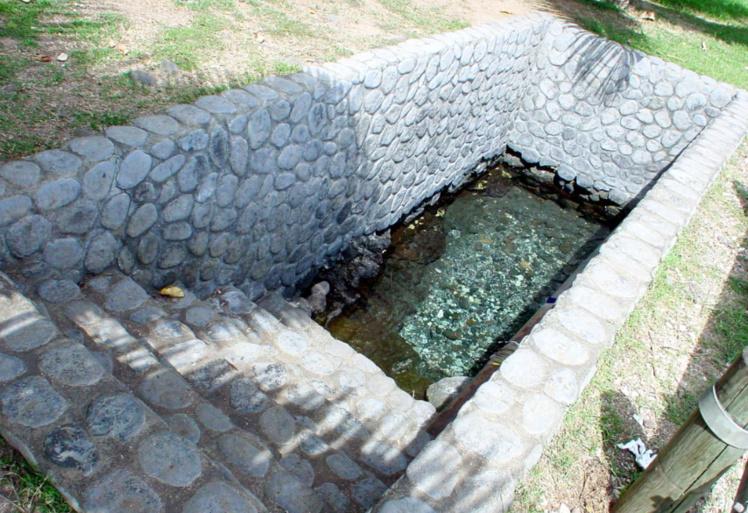 La source Vaipi'ihoro sépare les deux communes de Mahina et Papenoo. C'est à cet endroit, peu après le virage du village de Orofara, que les mamas des deux communes se rencontraient pour se baigner. A cette époque, les femmes se laissaient glisser sur l'eau de la source jusque la mer. Malheureusement, avec les agrandissements successifs de la route de ceinture, la source n'a pas été aménagé correctement et ressemble plutôt à un caveau humide. Photo Tahiti Heritage