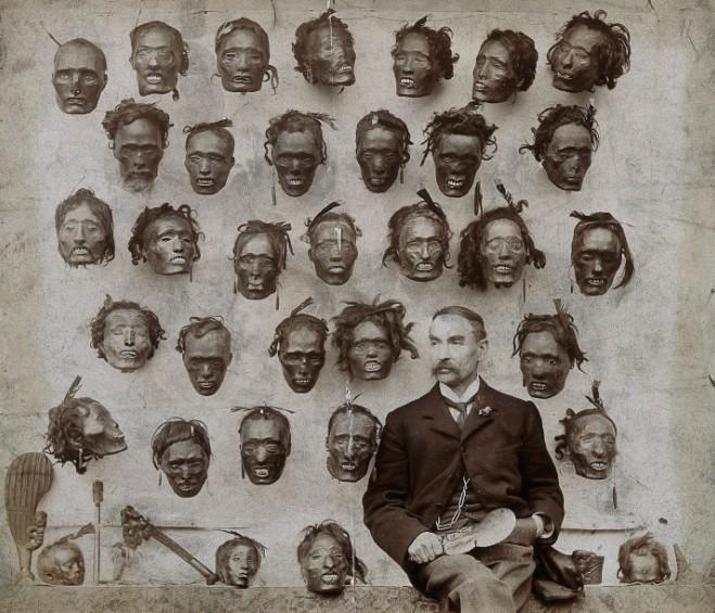 """Horatio Gordon Robley posant devant sa macabre collection de têtes maories. Le document semble horrible ; à l'époque, c'était une fierté que de s'afficher avec une telle """"moisson"""" de curiosités ethnologiques."""