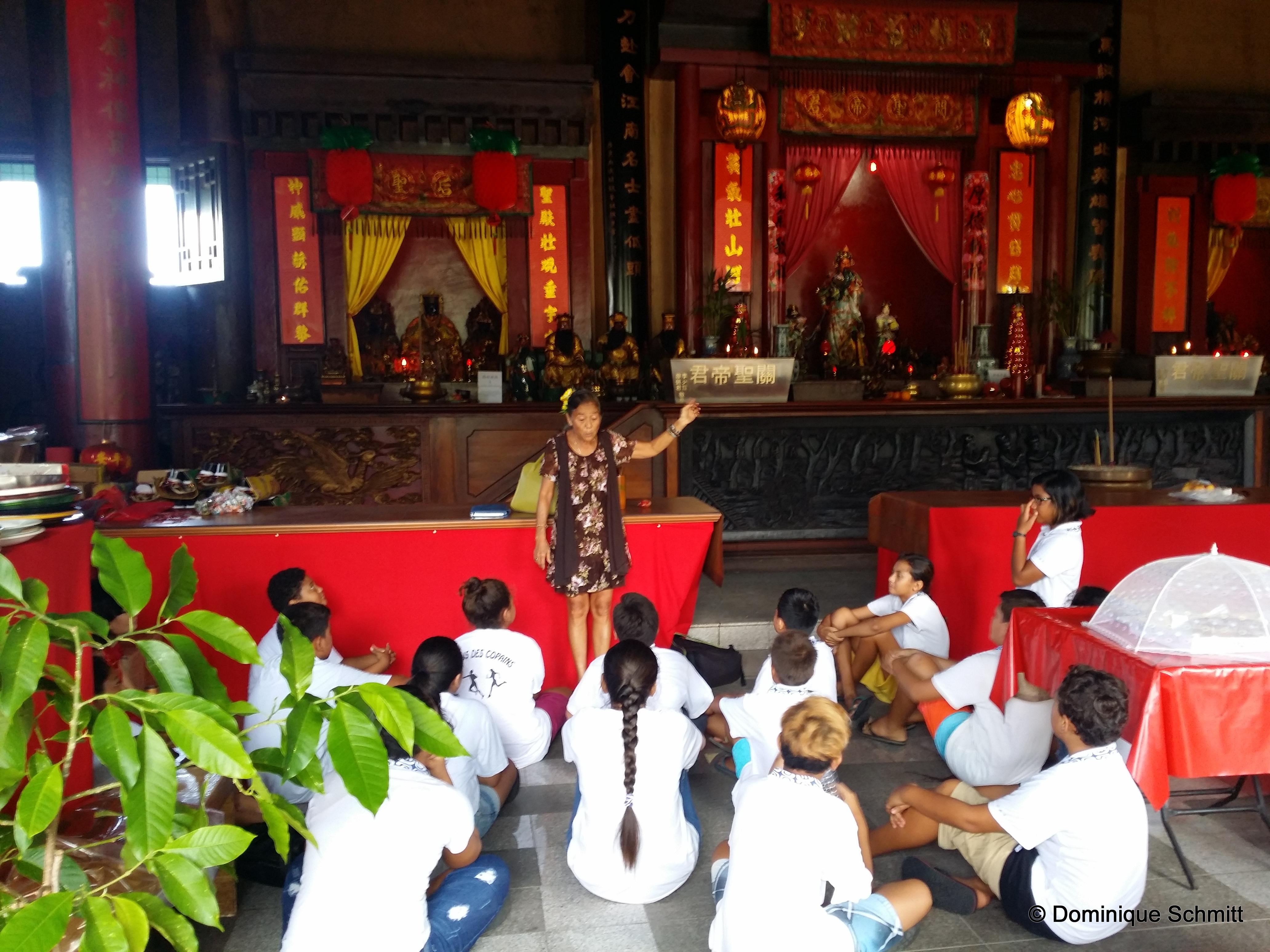 Des élèves du collège de Tiarama écoutent attentivement les explications de Germaine Chung, la responsable du Temple Kanti.