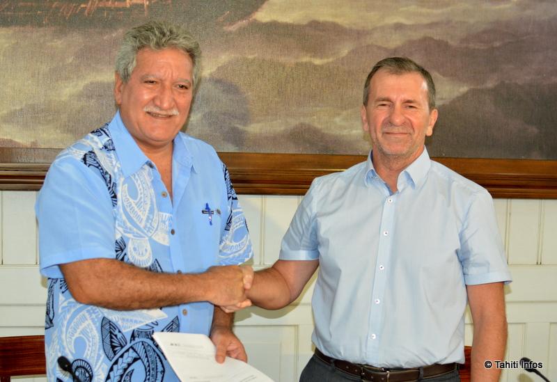 Jean-Christophe Bouissou, ministre en charge du Numérique, et Dominique Diot, représentant l'Agence Nationale des Fréquences, s'échangent la convention signée entre les deux entités.