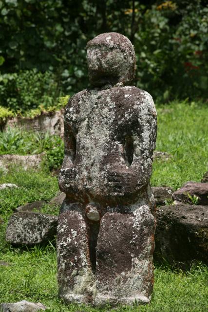 """Le tiki gris se nomme Te Ha'a Tou Mahi a Naiki ; son corps, trop gros par rapport à sa tête, montre que les deux pièces n'ont pas été sculptées ensemble ; en fait, il aurait été décapité puis tardivement """"rafistolé"""" avec la tête d'un autre tiki se trouvant sur le site."""