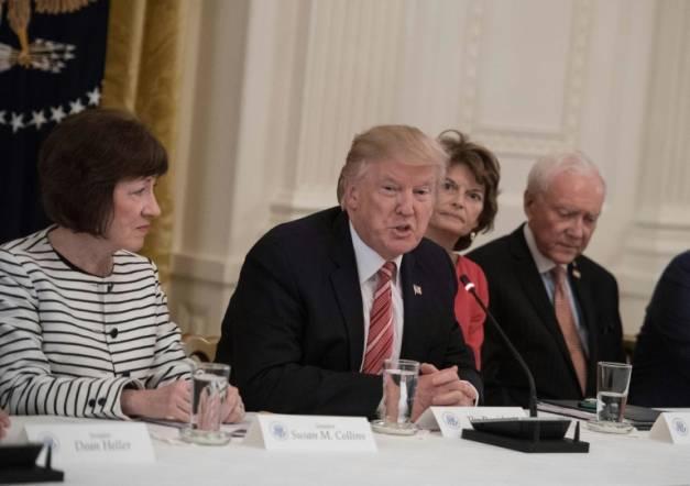 Le président américain Donald Trump entouré par les sénatrices républicaines Susan Collins (G) et Lisa Murkowski (D) le 27 juin 2017 à la Maison blanche à Washington ( AFP/Archives / NICHOLAS KAMM )