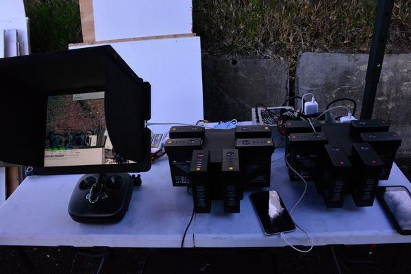 l'écran de surveillance vidéo des vols et des épandages (à gauche) et les jeux de batteries de rechange (à droite)