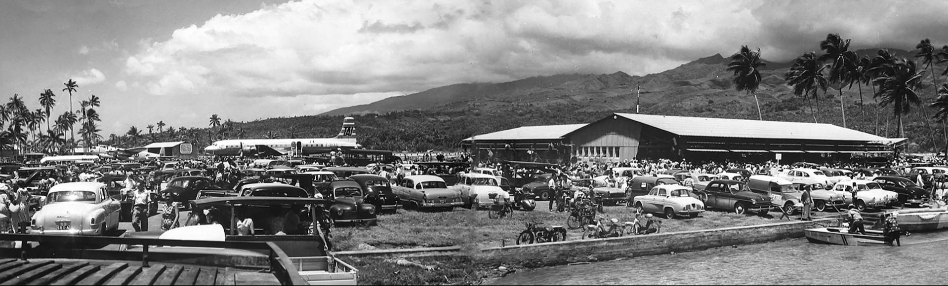 Sur le motu Tahiri, un exceptionnel rassemblement populaire accueille le DC 7C, premier avion commercial à s'être posé sur l'île en ce jour historique du 16 octobre 1960. À l'écart, à gauche de l'image, près des cocotiers, le Lancaster de la 9S de la Tontouta dont la mission est de photographier les atolls du sud des Tuamotu. Certains seront choisis comme bases du Centre d'expérimentations atomiques durant les trente-cinq années suivantes.
