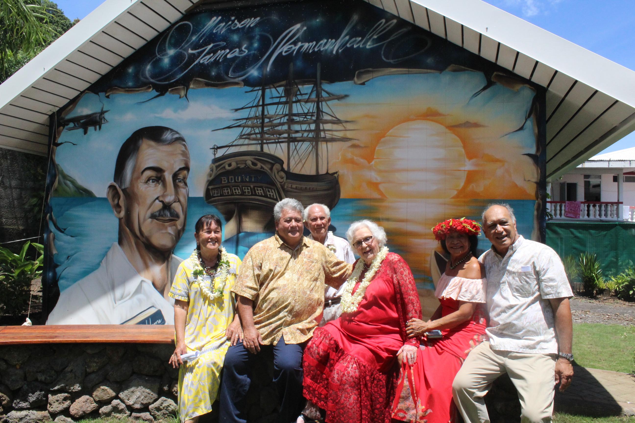 Nancy Hall-Rutgers, en robe rouge, entourée de ses proches devant la fresque représentant son père, James Norman Hall.