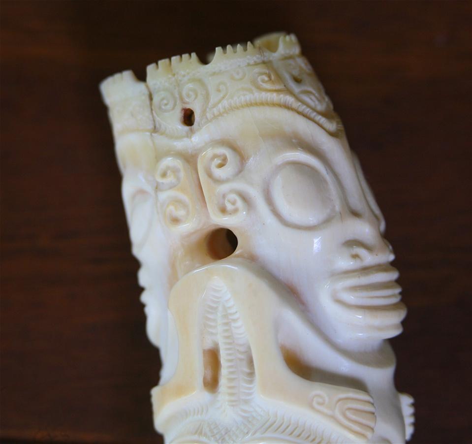 Gros plan sur la partie supérieure d'une dent de cachalot gravée.