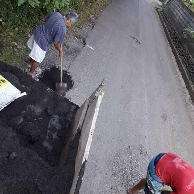 Pour minimiser les dégâts, papa Manarani et sa famille bouchent les nids de poule avec les moyens du bord.