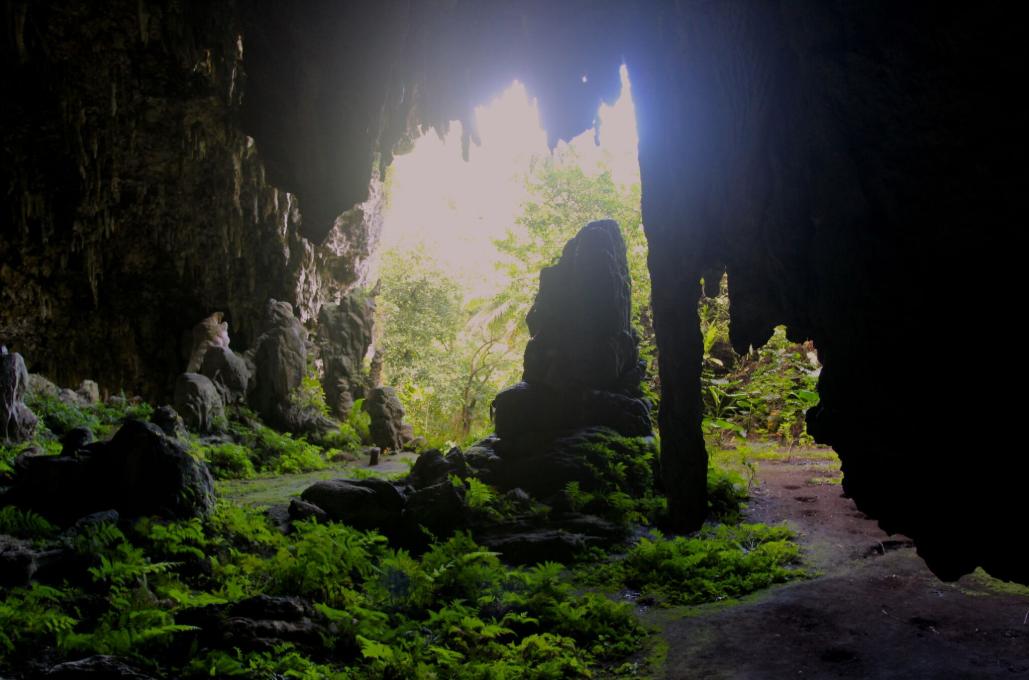 Contre-jour devant l'entrée principale. Un énorme stalagmite semble monter la garde au milieu du passage.