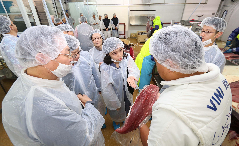 Après la découverte de la salle où est organisée la criée, la délégation s'est dirigée vers les ateliers de découpe du poisson frais. Crédit Présidence de la Polynésie française.