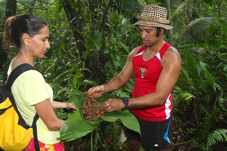 Heimana offrant à une touriste sa récolte de curcuma.