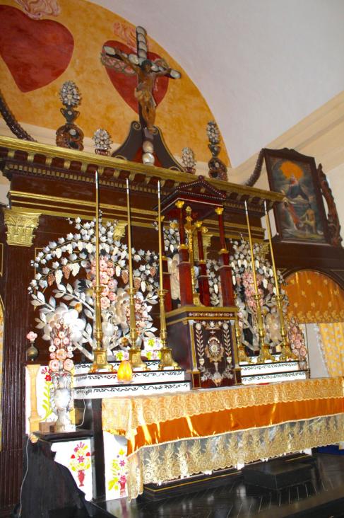 Le maître autel, fait d'une délicate dentelle de marqueterie, de nacre et de divers coquillages, surmonté des deux cœurs de Jésus et de Marie.