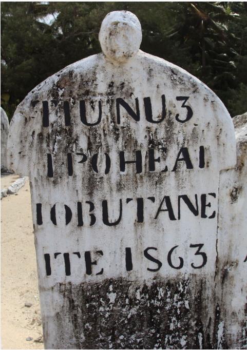 Dans le cimetière de Motuaura, une tombe classique surmontée d'une tête sculptée très érodée.