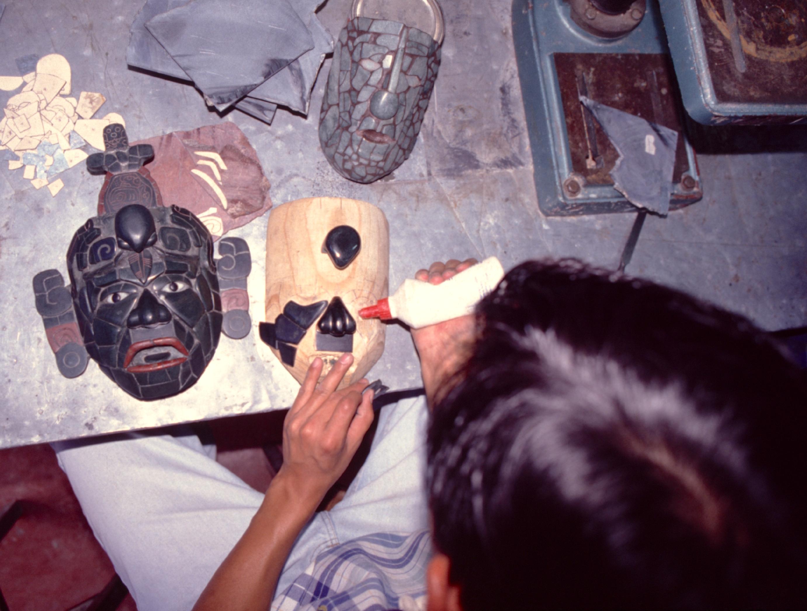 L'atelier d'un graveur ; les masques sont réalisés par collage des pièces de jade sur une forme en bois qui sera ensuite enlevée.