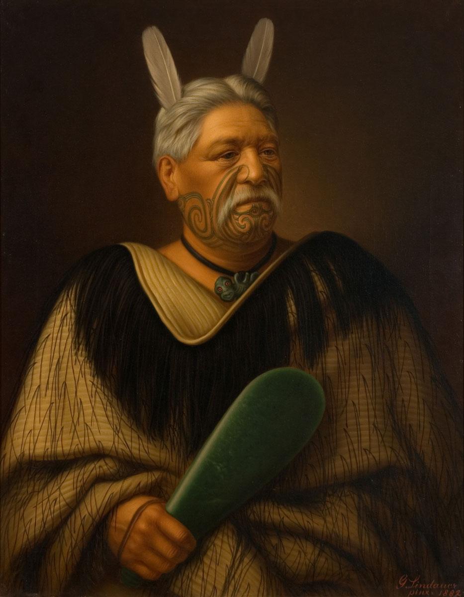 Un chef Maori portant autour du cou un hei tiki de jade et un casse-tête lui aussi en jade.