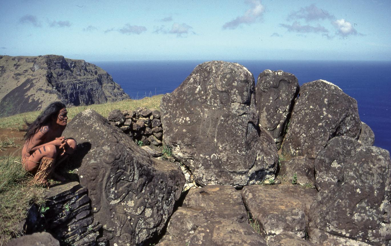 Comme jadis, sur le site le plus riche en pétroglyphes d'Orongo, un Pascuan observe les îlots au large, Motu Nui, Motu Iti et Motu Kaokao.