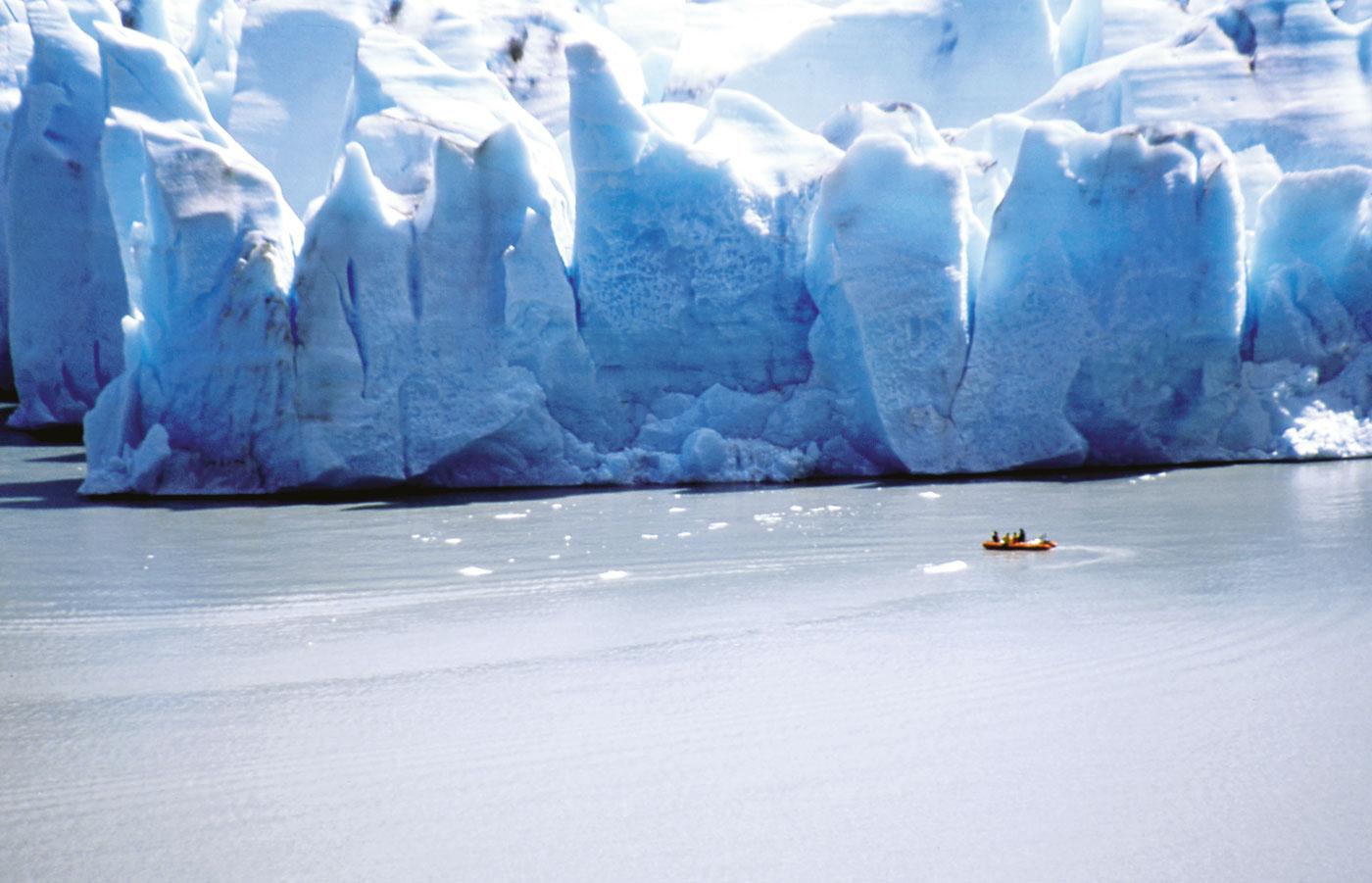 """Un zodiac vient """"renifler"""" le glacier de près. Le mur mesure trois kilomètres de long sur cinquante mètres de hauteur en moyenne."""