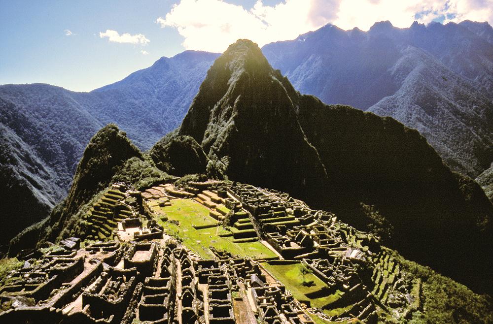 """Vue classique, depuis  les hauteurs de la cité, du Machu Picchu (les ruines) et du Huayna Picchu (le """"Jeune pic""""). Au sommet, des grottes étaient consacrées au culte de la lune. L'ascension est à éviter absolument si l'on est sujet au vertige..."""