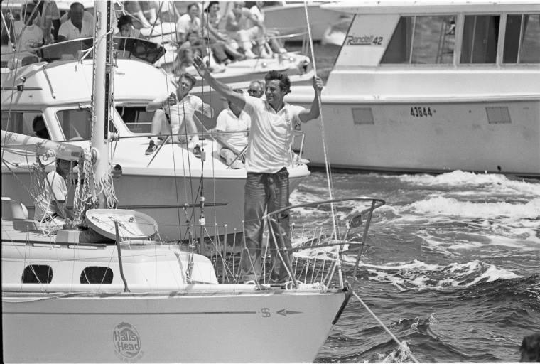 Photo prise le 31 octobre 1982 à son retour à Perth après un double tour du monde. Son bateau, le Perie Banou, est escorté dans l'embouchure de la Swan jusqu'au yacht club.