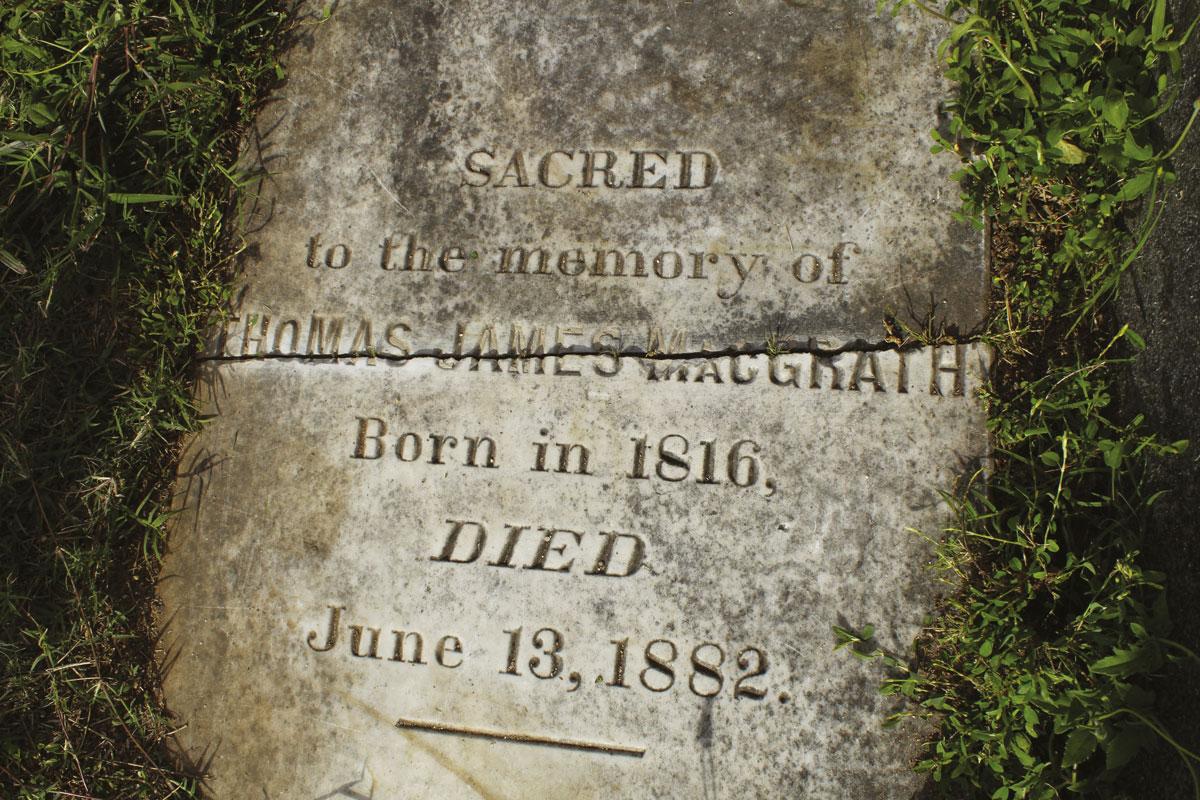 """La tombe de McGraph au premier niveau du cimetière de l'Uranie. L'herbe avait poussé sur la brisure de la dalle, rendant l'inscription du nom illisible. Mais il repose bien ici, jamais inquiété pour ses activités de blackbirding. En grattant la pierre tombale trouvée au cimetière de l'Uranie, à Papeete, l'identité du """"pensionnaire"""" est apparue : Thomas James MacGrath, à savoir McGraph le négrier."""