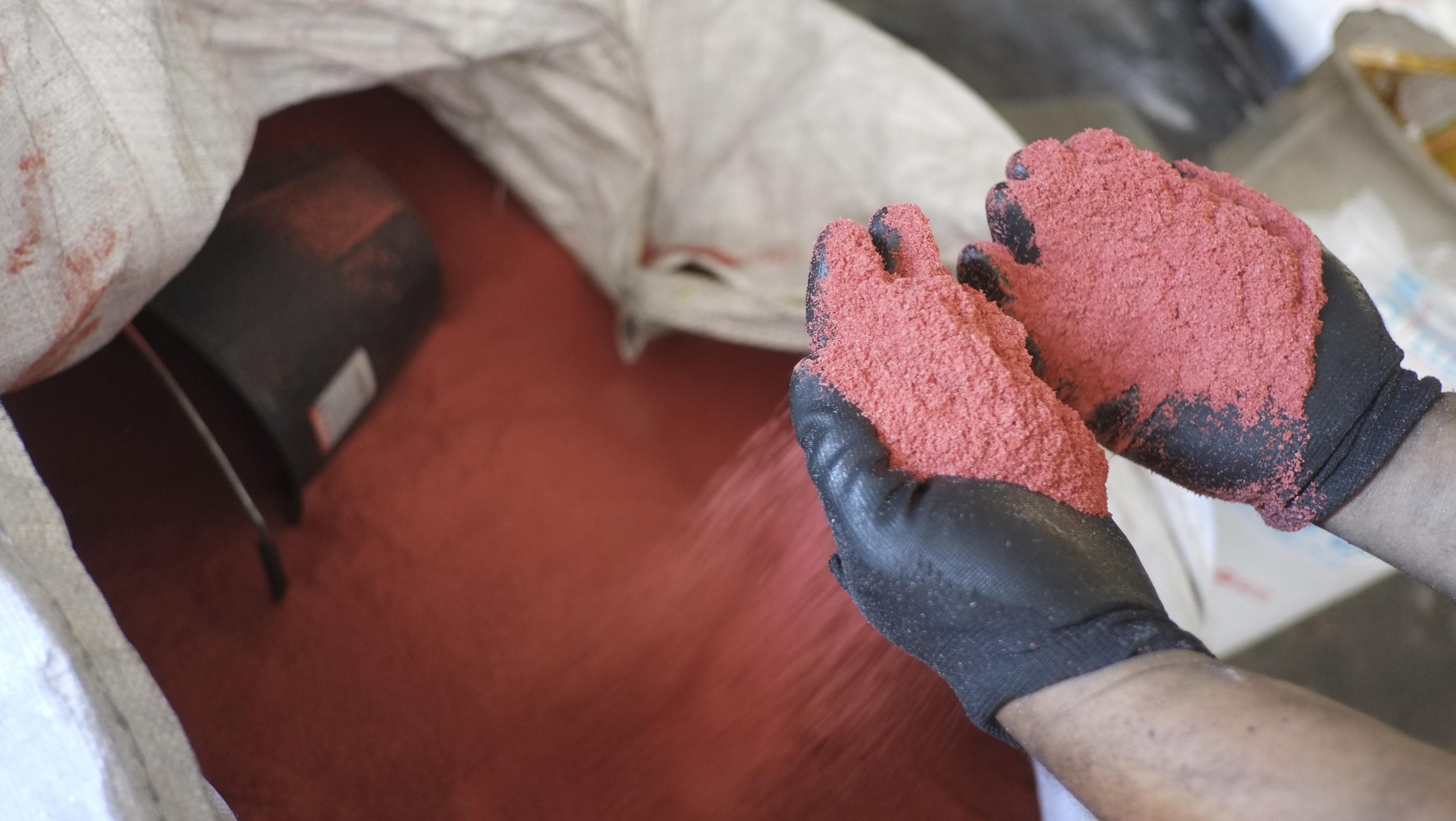 Le plastique est d'abord broyé en paillettes, qui sont à leur tour écrasées jusqu'à obtenir ce sable fin.