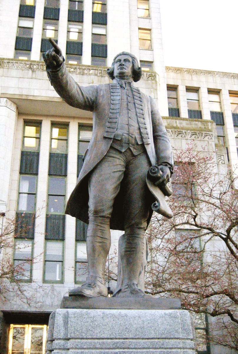 """La statue de George Vancouver orne un espace public, devant le """"city hall"""" de la ville qui porte son nom au Canada."""